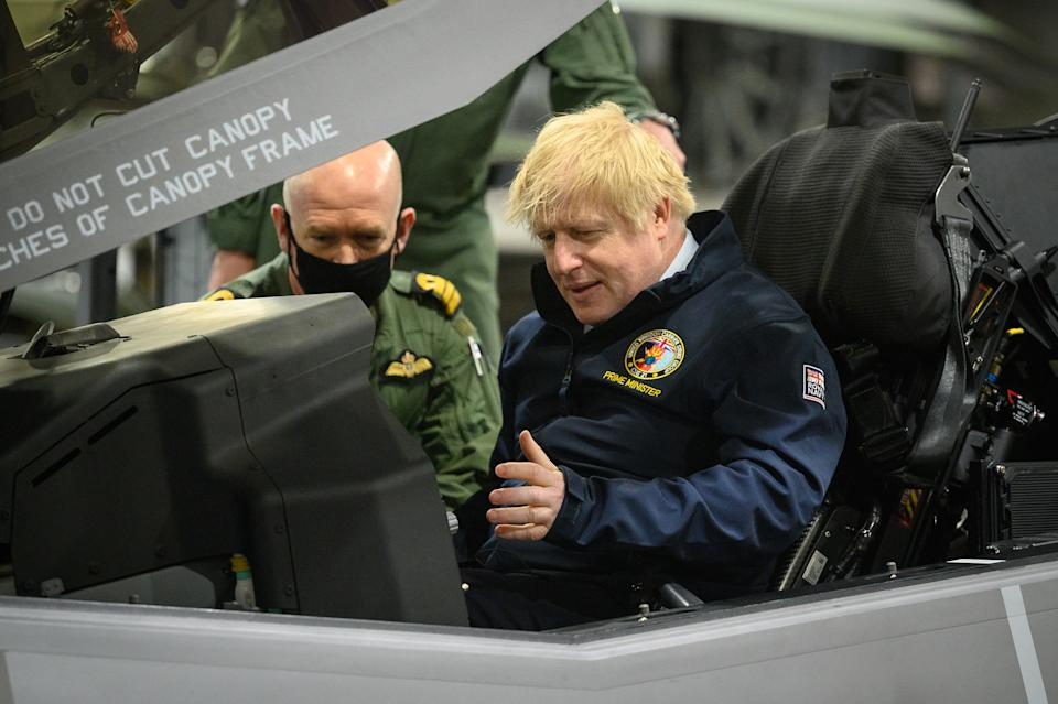 Prime Minister Boris Johnson sits in the cockpit of an Lockheed Martin F-35 Lightning II during a visit aboard HMS Queen Elizabeth in Portsmouth ahead of its first operational deployment to the Far East. Picture date: Friday May 21, 2021. (Photo by Leon Neal/PA Images via Getty Images)