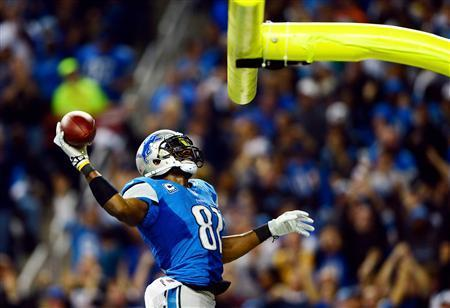 Detroit Lions wide receiver Calvin Johnson (81) dunks the football over the goal post after scoring a touchdown during the third quarter of a NFL football game against the Green Bay Packers on Thanksgiving at Ford Field. Mandatory Credit: Andrew Weber-USA TODAY Sports