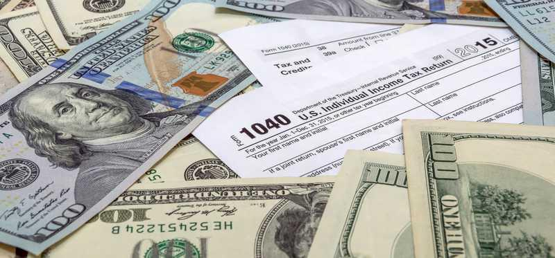 1040 tax form with money on top.