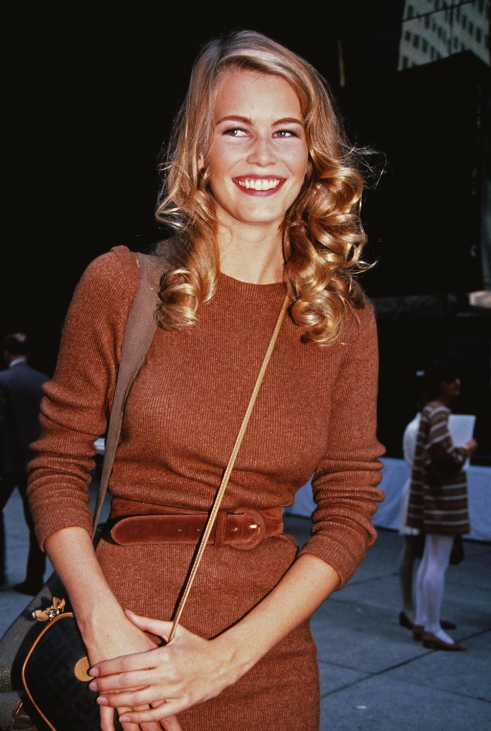 <p>Schiffer works 1990s power-dressing in this maroon-brown coloured jumper dress, 1992</p>