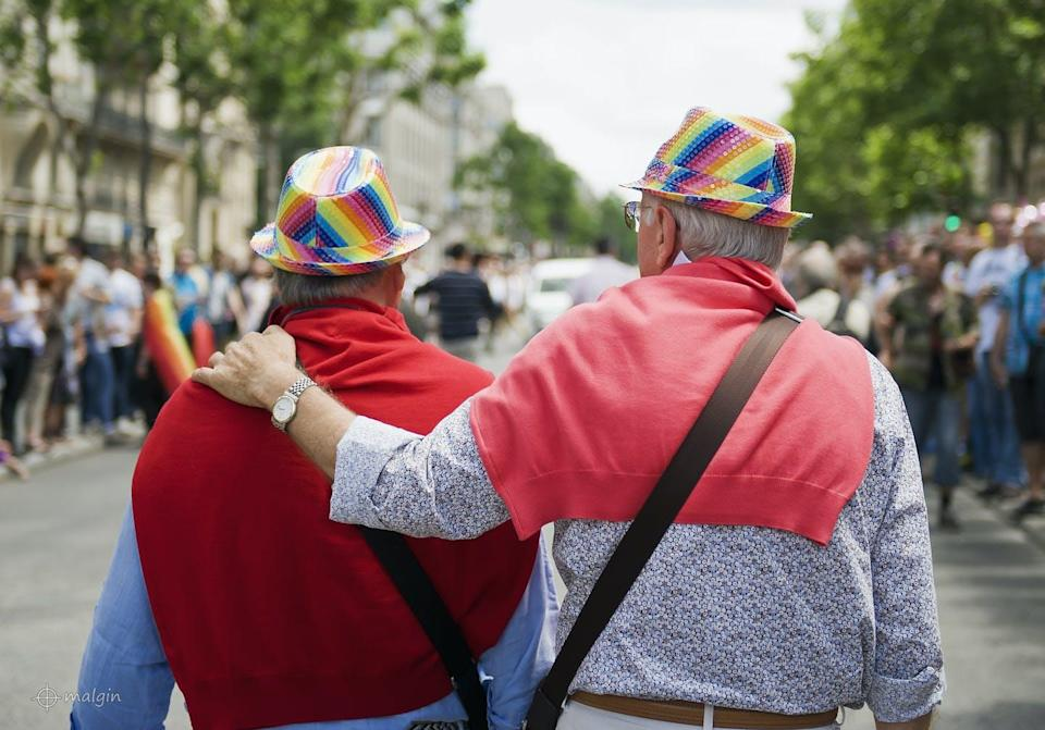 An elderly couple at a Pride parade seen from behind are wearing hats with the colours of the rainbow flag.