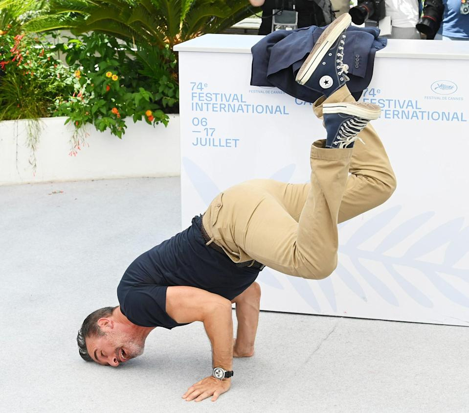 <p>Jean Dujardin shows off his moves during the <i>OSS 117: From Africa with Love</i> photo call at the Cannes Film Festival on July 17. </p>