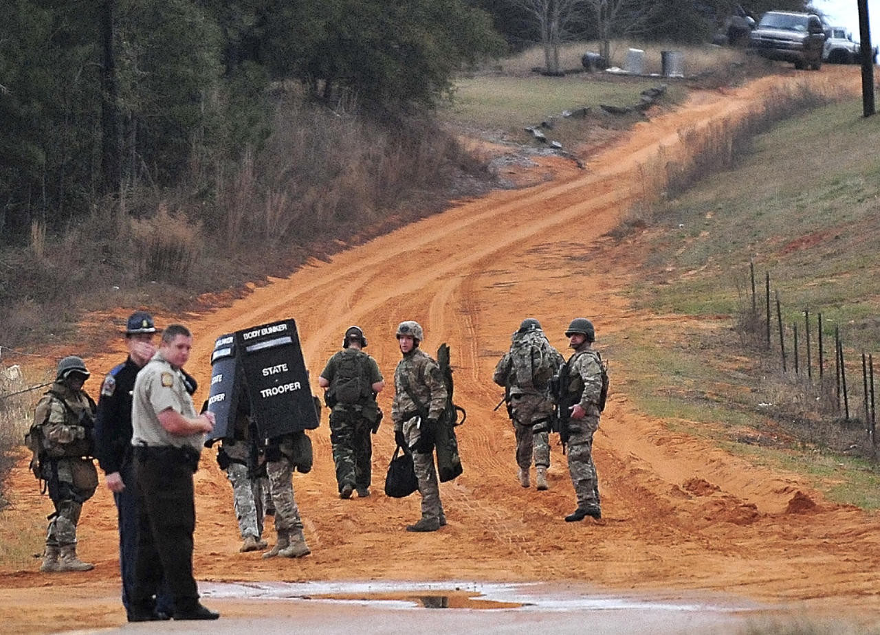 Law enforcement personnel work at check point Wednesday, Jan. 30, 2013, in Midland City, Ala., near the home where the Tuesday's school bus shooting suspect is barricaded in a bunker with a young child as hostage. Police, SWAT teams and negotiators were at a rural property where a man was believed to be holed up in a homemade bunker Wednesday after fatally shooting the driver of a school bus and fleeing with a 6-year-old child passenger, authorities said. (AP Photo/The Dothan Eagle, Jay Hare)