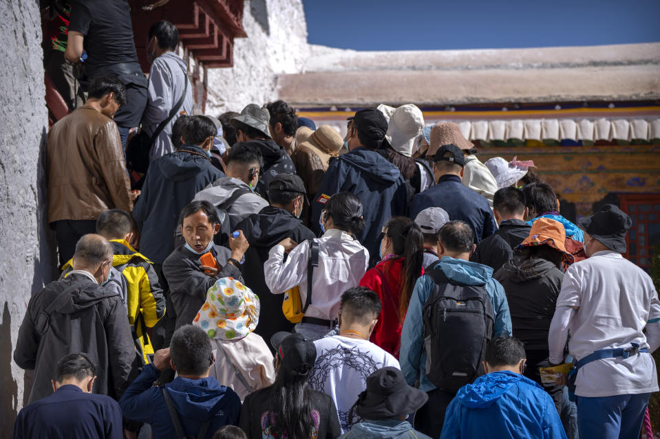 Tourists wait to climb steps to an interior area at the Potala Palace in Lhasa in western China's Tibet Autonomous Region, Tuesday, June 1, 2021. Tourism is booming in Tibet as more Chinese travel in-country because of the coronavirus pandemic, posing risks to the region's fragile environment and historic sites. (AP Photo/Mark Schiefelbein)