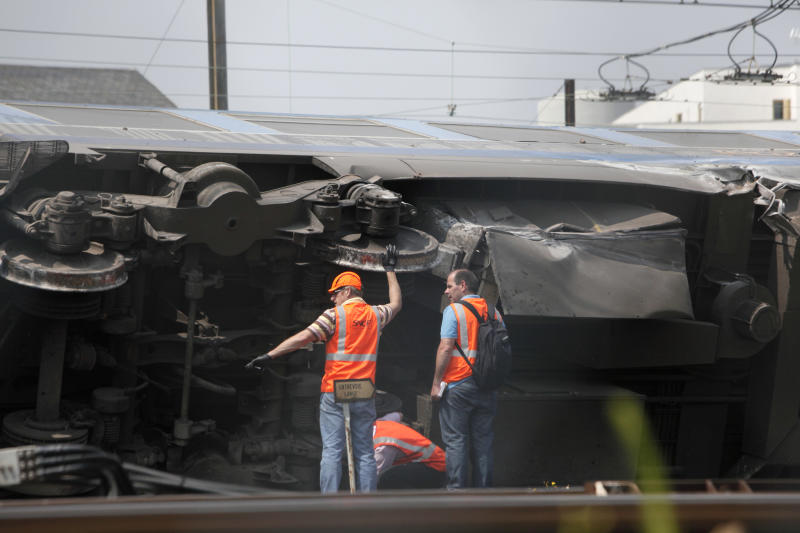 Railway's employees are seen on the scene where a train derailed at a station in Bretigny sur Orge, south of Paris, Saturday, July 13, 2013. An official on Saturday said a faulty rail joint may have caused a train derailment outside Paris that left six people dead and injured dozens. (AP Photo/Thibault Camus)