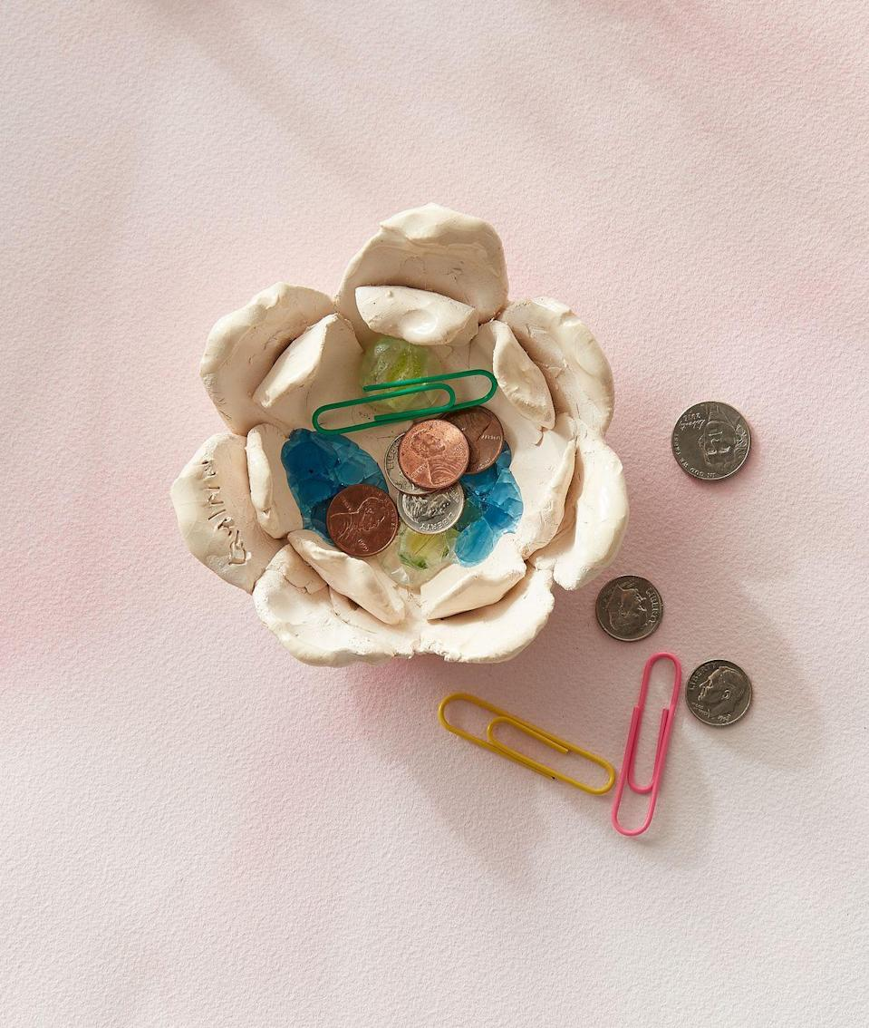 """<p>We know mom love all things organization, so what's better than a handmade bowl that she can use to corral loose change. To create your sculpture, use Sculpey (or another oven baked clay) to form a large flower petal. Form a smaller petal and press it into the center of the larger petal. Place plastic beads in bottom of the bowl. Bake, per package instructions, to melt plastic and harden clay.</p><p><a class=""""link rapid-noclick-resp"""" href=""""https://www.amazon.com/Polyform-Sculpey-Original-Polymer-1-75-Pound/dp/B0016N6CMU/?tag=syn-yahoo-20&ascsubtag=%5Bartid%7C10050.g.2357%5Bsrc%7Cyahoo-us"""" rel=""""nofollow noopener"""" target=""""_blank"""" data-ylk=""""slk:SHOP OVEN-BAKED CLAY"""">SHOP OVEN-BAKED CLAY</a></p>"""