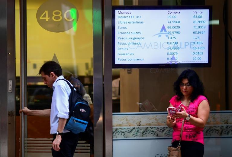Currency exchange values are displayed on the buy-sell board of a bureau de exchange in Buenos Aires, on October 28, 2019