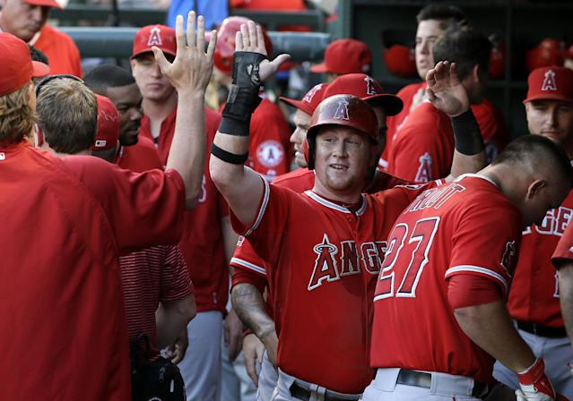 Los Angeles Angels' Kole Calhoun, center, is congratulated in the dugout after scoring on an Mike Trout three-run home run against the Texas Rangers in the third inning of a baseball game, Thursday, July 10, 2014, in Arlington, Texas. The shot also scored Hank Conger. (AP Photo/Tony Gutierrez)