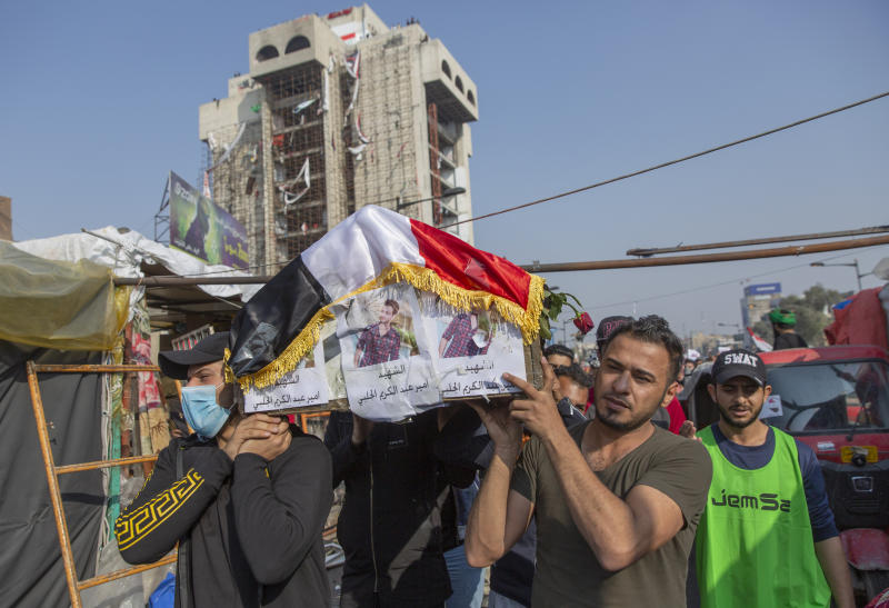 Mourners carry the body of their fellow protester Ameer al-Jalabi, posters with his name and picture on front, during his funeral in Tahrir Square, Baghdad, Iraq, Thursday, Dec. 26, 2019. Ameer succumbed to his wounds on Wednesday after being injured during anti-government demonstrations on October 27, 2019. (AP Photo/Nasser Nasser)