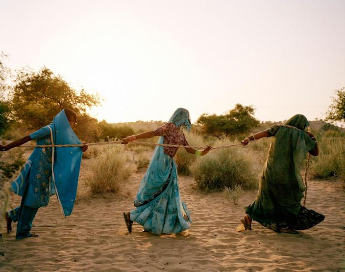 """<p>Women haul water from a 150-foot-deep well in the Thar desert, three hours' walk from their home in Bewatoo, Tharparkar, Sindh, Pakistan, 2013. Temperatures there hover at 48-50°C on summer days. With an extremely low water table and continuing drought, sometimes water must be hauled from a depth of 150 to 200 feet. """"Women fall unconscious on their way to these dug wells,"""" says Marvi Bheel, 45, a resident of Bewatoo, Tharparkar. From the water-scarce regions in southern Ethiopia to the desert wells of Pakistan, it is women who are primarily responsible for gathering water. (Photograph by Mustafah Abdulaziz/WaterAid) </p>"""