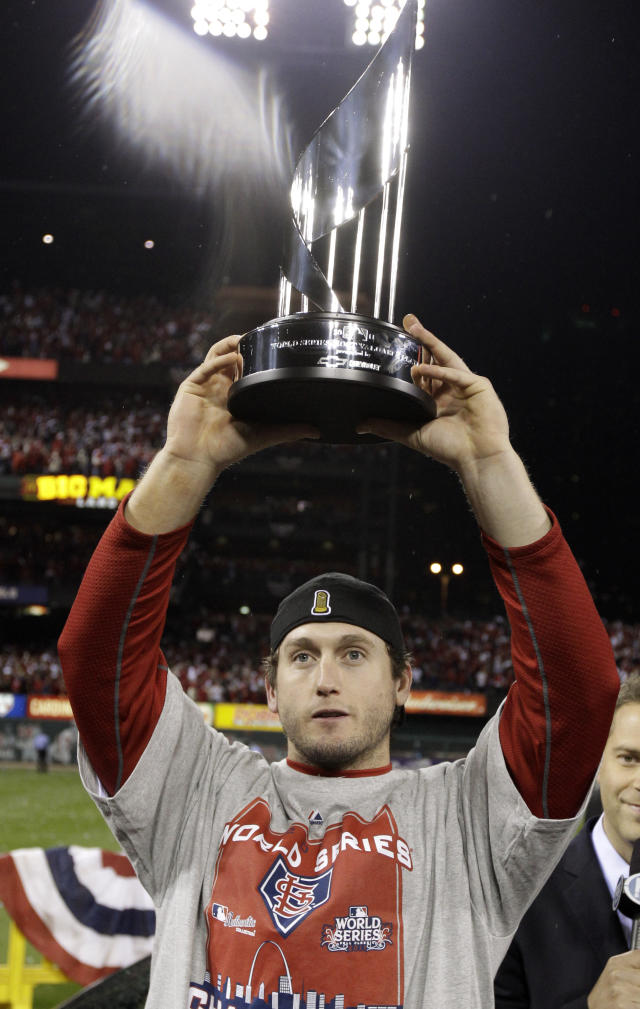 FILE - In this Oct. 28, 2011, file photo, St. Louis Cardinals' David Freese holds up the MVP trophy after Game 7 of baseball's World Series against the Texas Rangers in St. Louis. Freese is retiring after a 10-year career that included a World Series title in 2011 with the St. Louis Cardinals when he was MVP. The 36-year-old infielder made the announcement Saturday, Oct. 12, 2019, on his verified Twitter account. (AP Photo/Charlie Riedel< File)