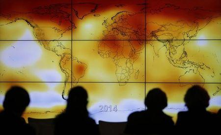 Participants are seen in silhouette as they look at a screen showing a world map with climate anomalies during the World Climate Change Conference 2015 (COP21) at Le Bourget, near Paris, France, December 8, 2015. REUTERS/Stephane Mahe