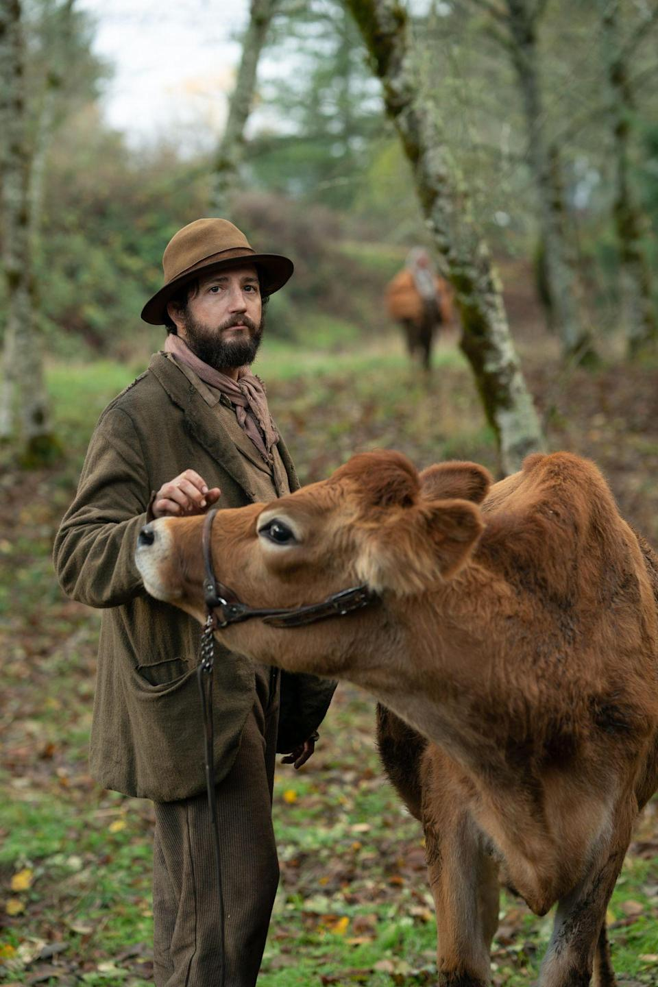 """<div class=""""caption""""> Cookie (John Magaro) and the first cow (Eve the cow). </div> <cite class=""""credit"""">Courtesy of A24</cite>"""