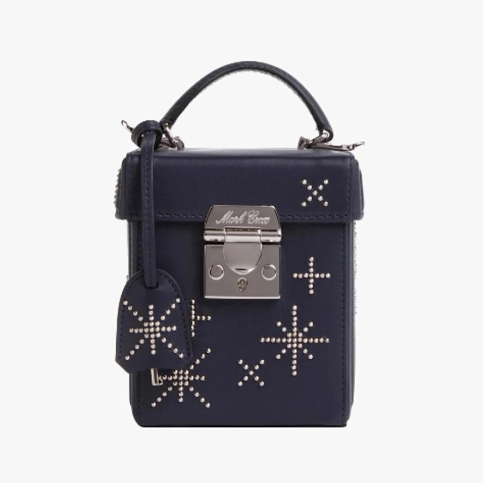 """$2590, MARK CROSS. <a href=""""https://www.markcross.com/collections/handbags/products/grace-cube-leather-box-bag-embellished-nappa-midnight-navy-palladium?variant=33100911935597"""" rel=""""nofollow noopener"""" target=""""_blank"""" data-ylk=""""slk:Get it now!"""" class=""""link rapid-noclick-resp"""">Get it now!</a>"""