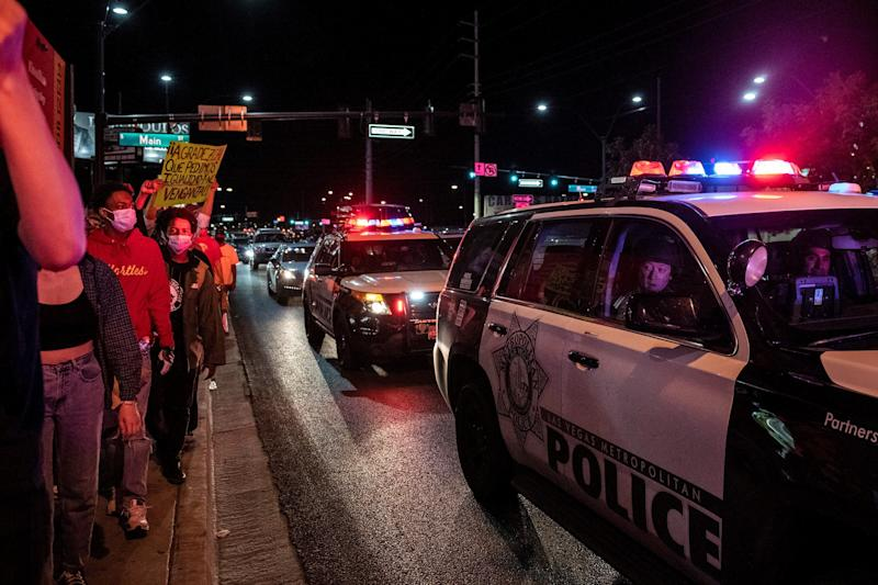 Police officers look outside their car window as people march in a Black Lives Matter rally in downtown Las Vegas on June 1. (Photo: BRIDGET BENNETT via Getty Images)