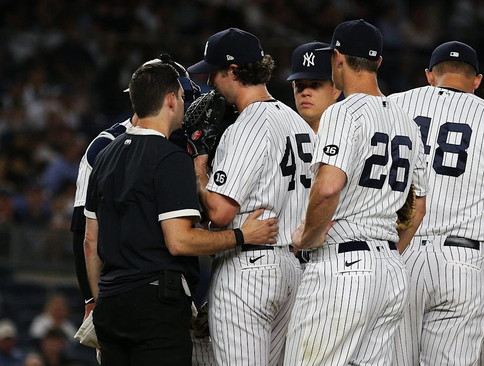 New York Yankees starting pitcher Gerrit Cole (45) is looked at by the trainer against the Toronto Blue Jays during the fourth inning at Yankee Stadium.