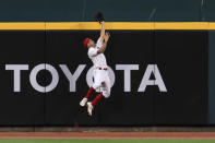 Cincinnati Reds' Nick Senzel leaps into the wall to make a catch against Kansas City Royals' Ryan O'Hearn in the fifth inning during a baseball game at in Cincinnati, Wednesday, Aug. 12, 2020. Kansas City Royals' Salvador Perez (13) would score on the sacrifice fly. (AP Photo/Aaron Doster)