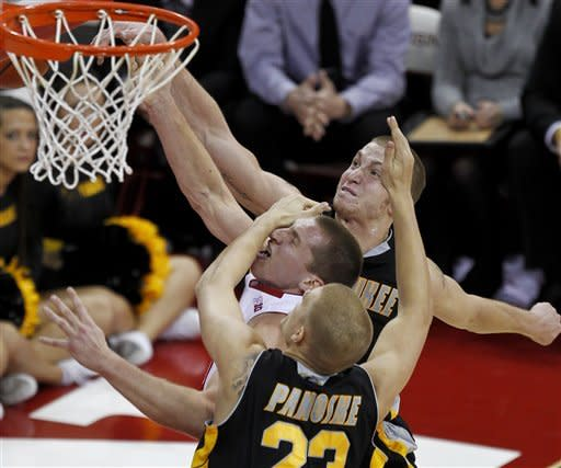 Milwaukee's J.J. Panoske fouls Wisconsin's Jared Berggren, center, during the first half of an NCAA college basketball game Saturday, Dec. 22, 2012, in Madison, Wis. At rear is Milwaukee's James Haarsma. (AP Photo/Andy Manis)