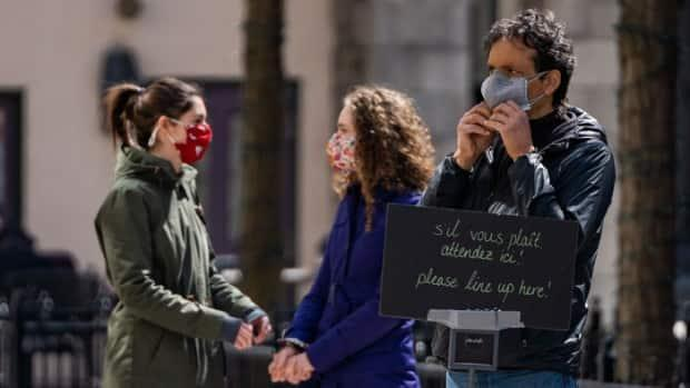 A man adjusts his mask while waiting in outdoor line in Ottawa on April 3, 2021. Saturday was the first day of Ontario's 'emergency brake' measures designed to halt the spread of COVID-19. (Mathieu Theriault/Radio-Canada - image credit)