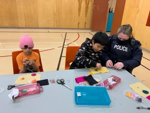 RCMP member Heather Cosenzo helps Hunter with his beading project in Ndilo on Thursday. (Alice Twa/CBC - image credit)