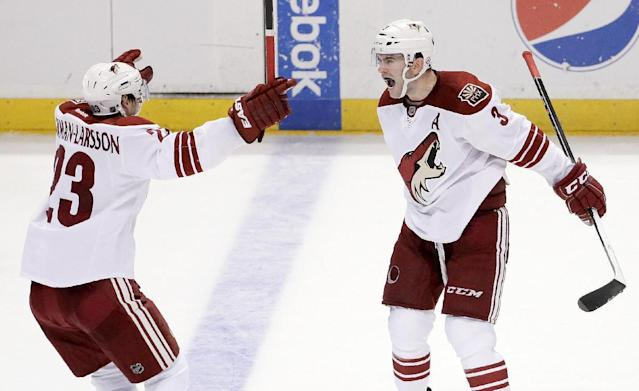 Phoenix Coyotes defenseman Keith Yandle, right, celebrates his goal with defenseman Oliver Ekman-Larsson during the third period of an NHL hockey game against the Anaheim Ducks in Anaheim, Calif., Saturday, Dec. 28, 2013. (AP Photo/Chris Carlson)