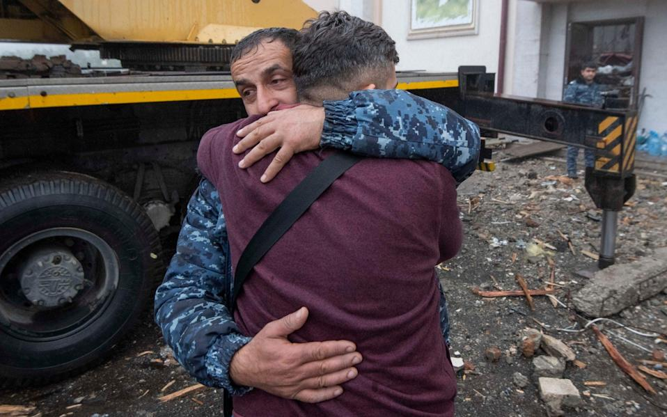 People grieve as bodies were removed from a central building in Shushi, hit by a missile on Sunday. Hostilities resumed between Armenian and Azerbaijan forces over the contested region of Nagorno-Karabakh on Oct 5th - JULIAN SIMMONDS