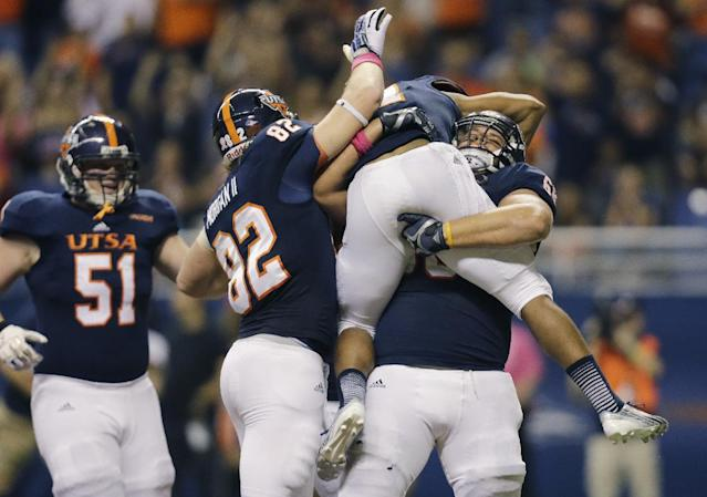 UTSA's Cody Harris, right, picks up teammate David Glasco II who scored a touchdown against Rice during the first half of an NCAA college football game on Saturday, Oct. 12, 2013, in San Antonio. UTSA's Payton Rion (51) and David Morgan II (82) also celebrate. (AP Photo/Eric Gay)