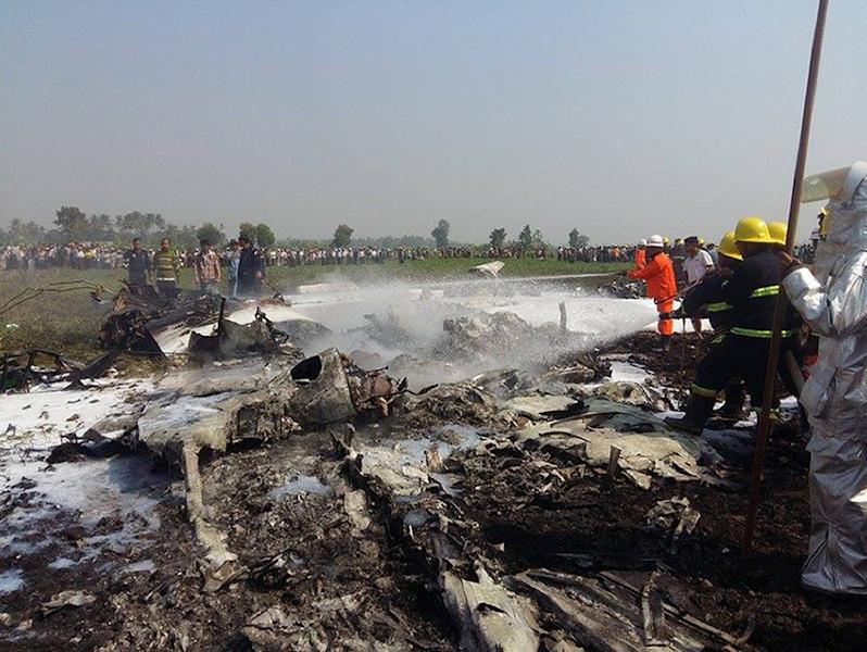 Firefighters spray the wreckage of a military passenger plane near the airport in the capital of Nayphidaw on February 10, 2016 (AFP Photo/Aung Htet)