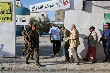 Army soldiers stand guard as people queue to cast their vote at a polling station in Tunis