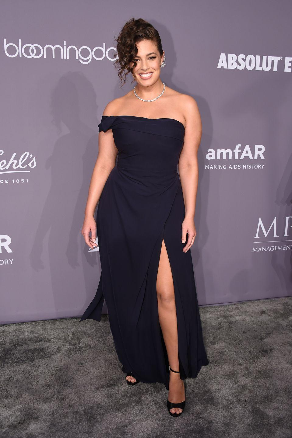 <p>Attending the amFAR Gala in New York: Step aside Angelina because Ashley Graham is here to take your thigh-high split dress crown. Looking stunning in her strapless navy gown, Ashley accessorised with some seriously '80s inspired curls. </p>