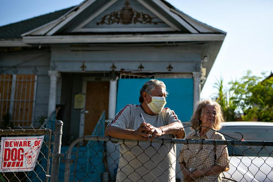 Candido Juarez and his wife stand in front of their homes that is uninhabitable after massive fireworks explosion June 30.