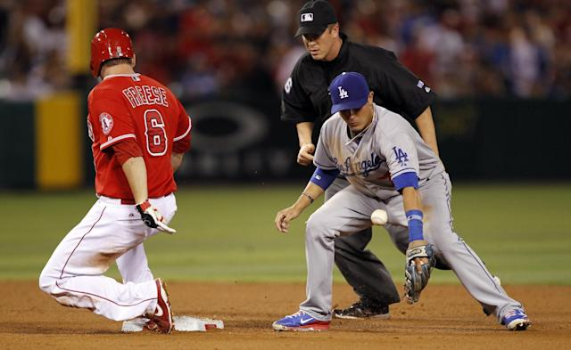 Los Angeles Dodgers shortstop Miguel Rojas, right, loses the ball on the throw from the outfield, as Los Angeles Angels' David Freese (6) slides into second base with a double, as umpire Chris Segal, center, watches in the fifth inning of a baseball game Thursday, Aug. 7, 2014, in Anaheim, Calif. (AP Photo/Alex Gallardo)