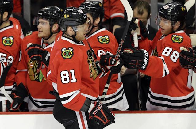 Chicago Blackhawks' Marian Hossa (81) celebrates with teammates after scoring his goal during the first period of an NHL hockey game against the Boston Bruins, Sunday, Jan. 19, 2014, in Chicago. (AP Photo/Nam Y. Huh)
