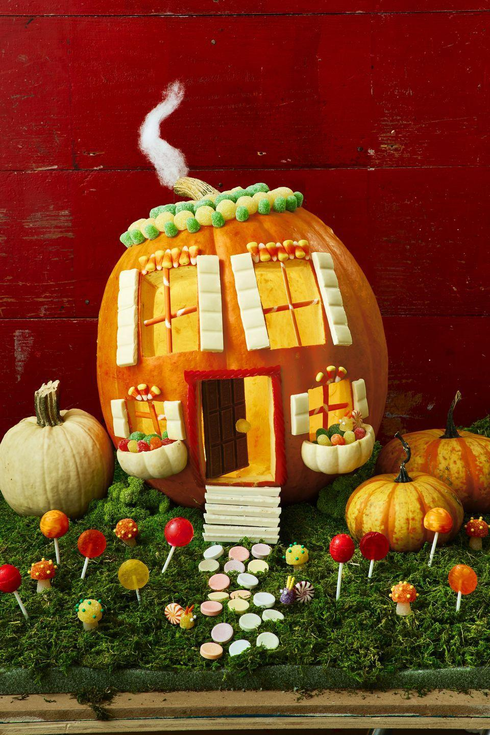 <p>Carve a round opening on top of pumpkin and hollow out insides. Carve out 3 rectangles on front for windows and doors. Place pumpkin on a slight hill of craft foam covered in moss. Cut off top of a white Jack Be Little pumpkin, then cut remaining pumpkin in half to form window boxes. Use T-pins to attach to house. Glue on details like polyester batting for smoke, gumdrops for roof, and white chocolate for shutters. Cut sugar straws into sections to fit snugly into window as frames. For door, glue a gumdrop doorknob to the front of a chocolate bar, then place in licorice- adorned doorway. Use craft foam to create a small hill, then layer pieces of white chocolate on top for steps.</p>