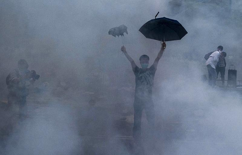 A pro-democracy demonstrator gestures after police fired tear gas near the Hong Kong government headquarters on September 28, 2014 (AFP Photo/Xaume Olleros)