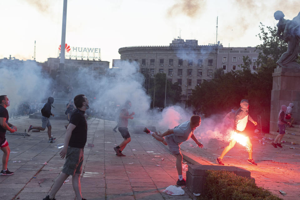 Protesters charge the building of the Serbian parliament in Belgrade, Serbia, Wednesday, July 8, 2020. Police have fired tear gas at protesters in Serbia's capital during the second day of demonstrations against the president's handling of the country's coronavirus outbreak. President Aleksandar Vucic backtracked on his plans to reinstate a coronavirus lockdown in Belgrade this week, but it didn't stop people from firing flares and throwing stones while trying to storm the downtown parliament building. (AP Photo/Marko Drobnjakovic)