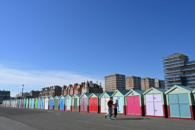 Once a day outside exercise is permitted, allowing these joggers to run past beach huts in Brighton on England's south coast (AFP Photo/Glyn KIRK)