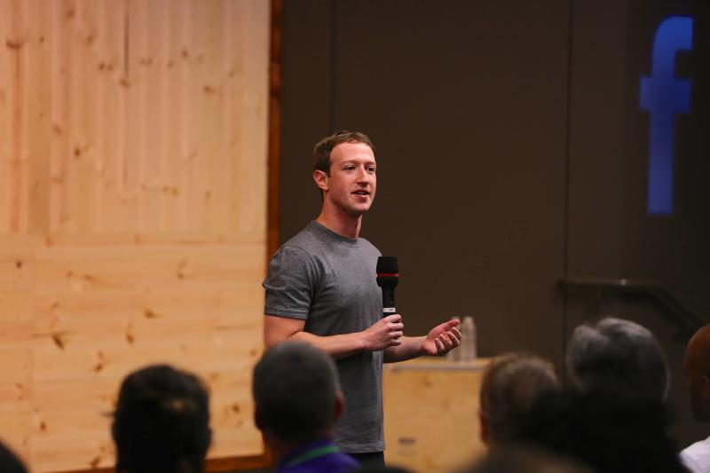 Facebook CEO Mark Zuckerberg holds a microphone as he addresses an audience.