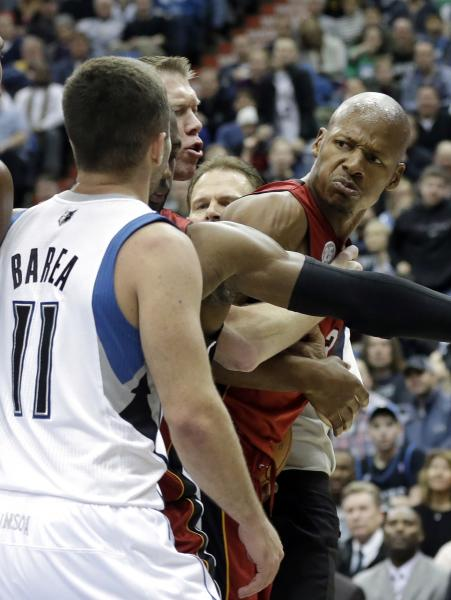 Miami Heat's Ray Allen, right, is separated by a teammate and an official is he jaws with Minnesota Timberwolves' J.J. Barea in the second half of an NBA basketball game Monday, March 4, 2013, in Minneapolis. Barea was ejected after a flagrant foul was called on him. The Heat won 97-81. (AP Photo/Jim Mone)