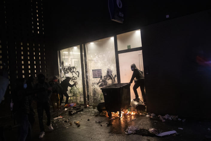 Protestors outside a police office in the Belgium capital, Brussels, Wednesday, Jan. 13, 2021, at the end of a protest asking for authorities to shed light on the circumstances surrounding the death of a 23-year-old Black man who was detained by police last week in Brussels. The demonstration in downtown Brussels was largely peaceful but was marred by incidents sparked by rioters who threw projectiles at police forces and set fires before it was dispersed. (AP Photo/Francisco Seco)
