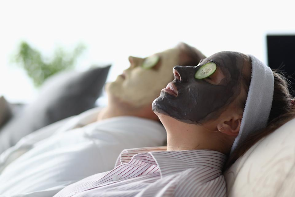Man and woman lie with mask their faces cucumbers. Couple lying on bed with cosmetic mask on face. Relaxation during self-isolation. Cleansing and matting masks for skin prone to greasy