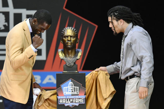 FILE - In this Aug. 4, 2018, file photo, former NFL wide receiver Randy Moss, left, unveils his bust with his presenter, son Thaddeus Moss, during induction ceremonies at the Pro Football Hall of Fame in Canton, Ohio. In the Southeastern Conference, the Manning family is just the best known example of sons following their fathers, and in many cases, grandfathers into football. Turns out teams across the league have players living out their own family legacies.(AP Photo/David Richard, File)