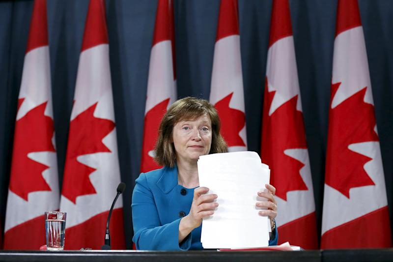 Canada's Information Commissioner Legault shuffles papers during a news conference in Ottawa