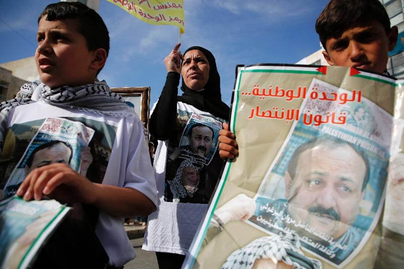 Palestinians hold portraits of Palestinian leader and prominent prisoner Marwan Barghouti, during a rally in the West Bank city of Ramallah in support of prisoners on hunger strike in Israeli jails on April 24, 2017