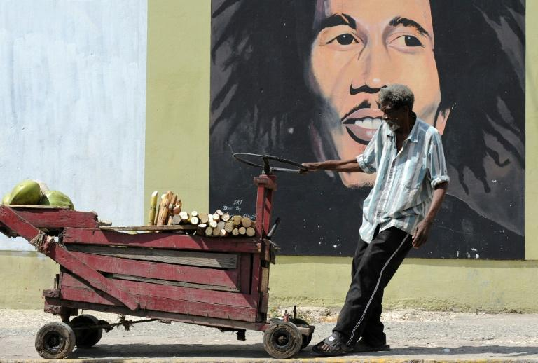 A vendor pulls a cart in this 2009 file photo in front of a mural of Bob Marley in Kingston, where reggae legend Bunny Wailer, the last surviving member of The Wailers, has died