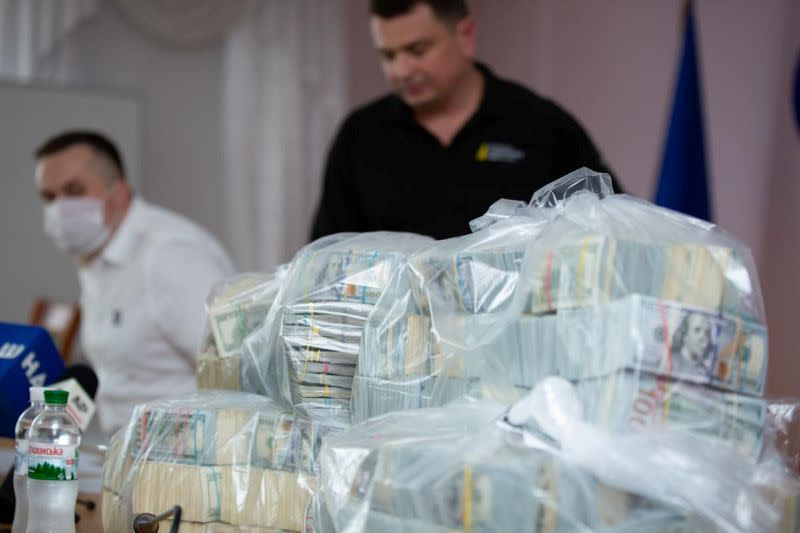 Plastic bags filled with U.S. Dollar banknotes seized by the National Anti-Corruption Bureau of Ukraine are seen on a table during a news briefing in Kiev
