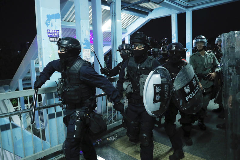 Riot police gather outside the Yuen Long MTR station during a protest in Hong Kong, Wednesday, Aug. 21, 2019.  Hong Kong riot police faced off with protesters occupying a suburban train station Wednesday evening following a commemoration of a violent attack there by masked assailants on supporters of the anti-government movement. (AP Photo/Kin Cheung)