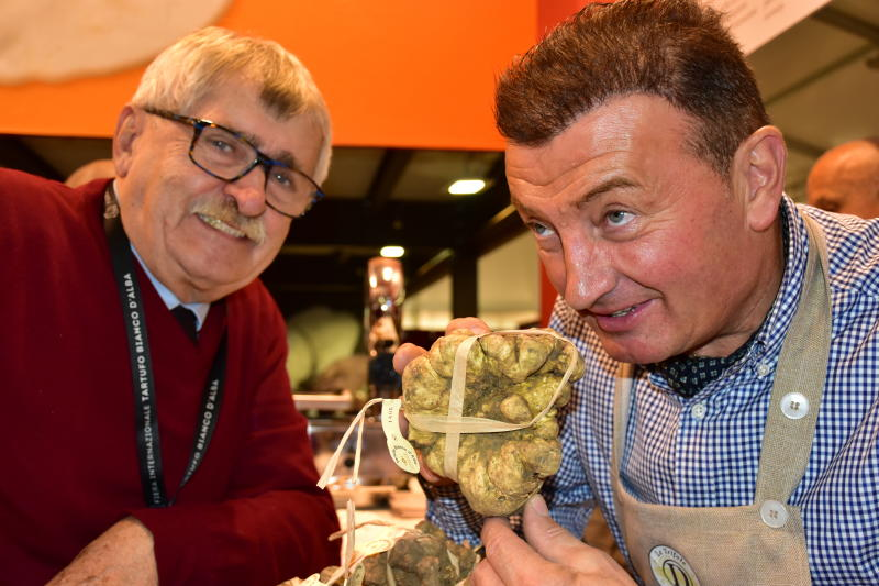 In this photo taken on Saturday, Nov. 9, 2019, Davide Curzietti, right, shows off a 730-gram truffle to judge Natale Romagnolo at the Alba Truffle Fair, established as a place to trade the highly prized and aromatic white truffles that grow in the hills around the southern Piedmont town of Alba in northern Italy. (AP Photo/Martino Masotto)