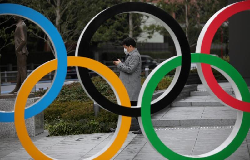 FILE PHOTO: Man wearing protective face mask looks at his mobile phone next to The Olympic rings in front of the Japan Olympics Museum in Tokyo