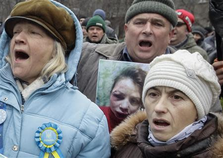 A protester holds a picture of journalist Tetyana Chornovil, who was beaten and left in a ditch just hours after publishing an article on the assets of top government officials, during a protest rally in front of the Ukrainian Ministry of Internal Affairs in Kiev December 25, 2013. REUTERS/Stringer